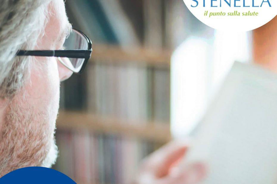 Uomo anziano con occhiali allontana un foglio per leggerlo